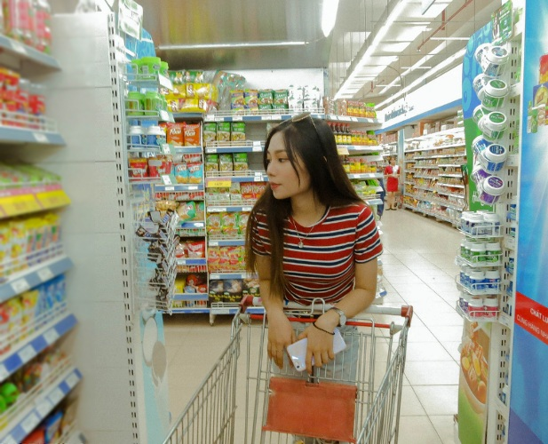 Asian woman leaning on shopping cart in the grocery store