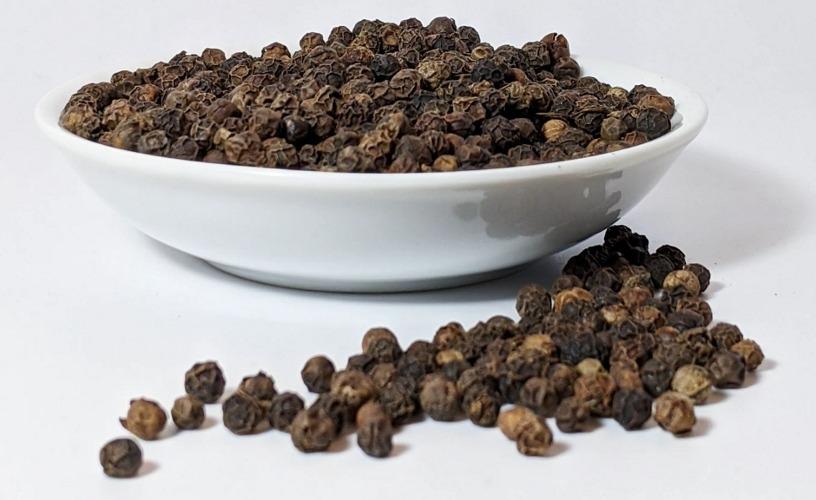 Black peppercorns in white ceramic bowl