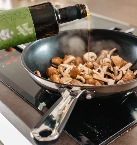 pouring dry sherry wine into a pan of frying mushrooms
