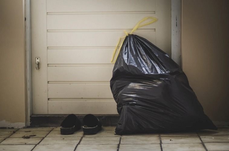 Black trash bag in front of white door