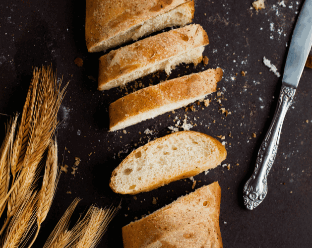 Wheat bread slices in between knife and wheat grains