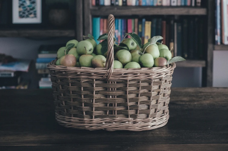 A basket of green apples on a table