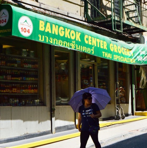 Woman with blue umbrella walking in front of Bangkok Center Grocery store
