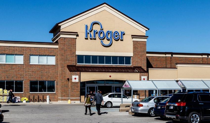 Man and woman walking towards Kroger supermarket building entrance