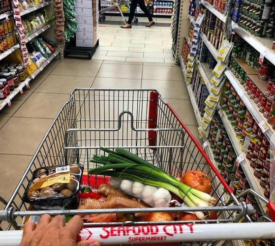 Shopper wheeling Seafood City Supermarket cart containing grocery items