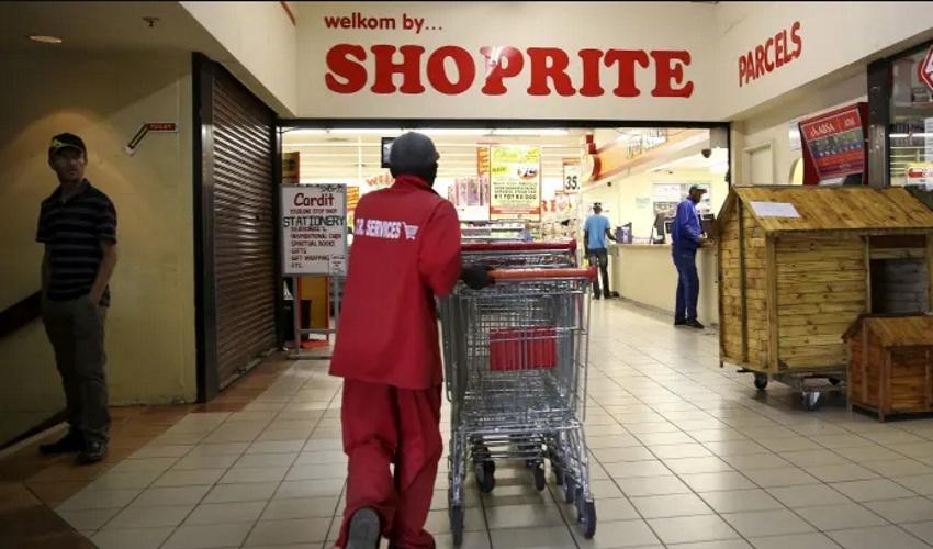 Shoprite employee wheeling shopping carts into a Shoprite outlet