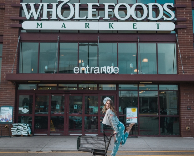 Smiling woman with shopping cart in front of Whole Foods Market entrance