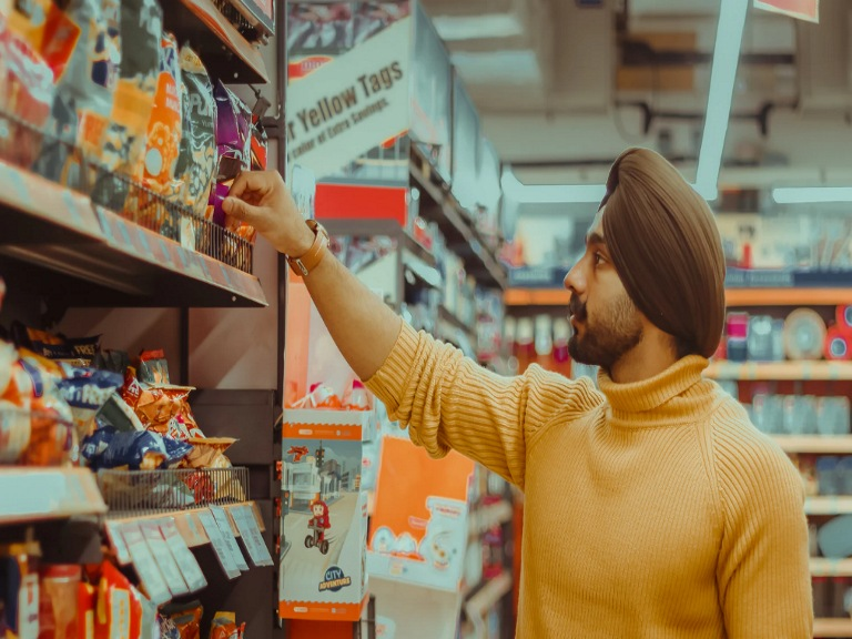 Man reaching for item on a grocery store shelf