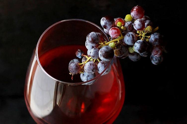 A glass of juice with grapes resting on the lip