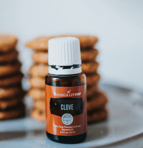 Clove oil bottle standing in front of a plate of cookies