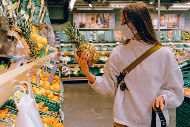Girl holding a pineapple in a grocery store