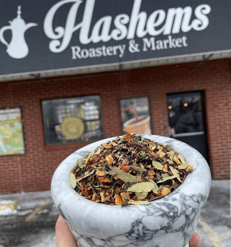 Hand holding up a bowl of spices in front of Hashems Roastery and Market