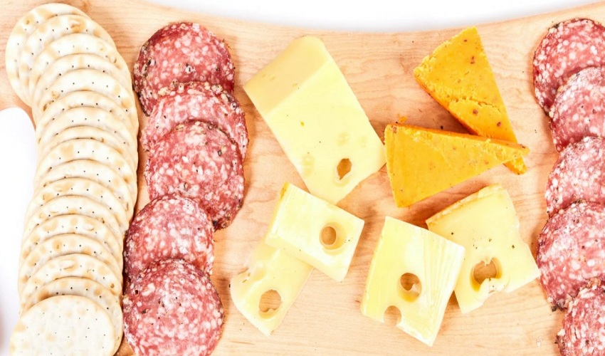 Swiss cheese on a wooden board with salami and biscuits