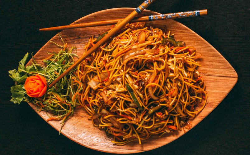 Yakisoba noodles in a wooden plate with chop sticks