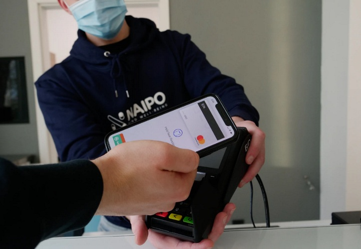 Man holding iPhone close to a POS machine