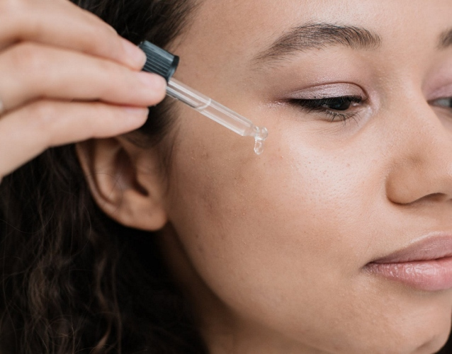 Girl applying oil with an applicator to her face