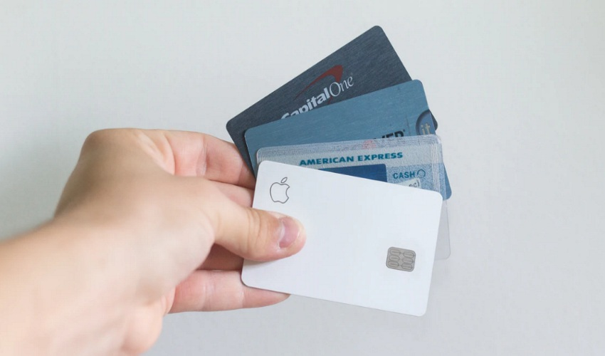 Hand holding four credit cards against a white background